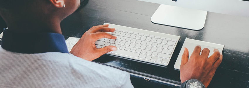 Image shows a man's hands typing on a keyboard
