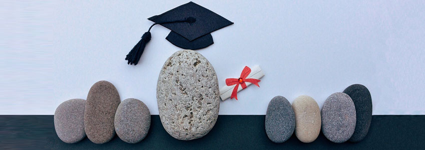 A group of stones, with one wearing a graduation cap