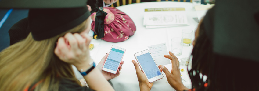 Graduating students using a smartphone